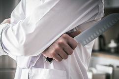 Kitchen Chef with Knife. Caucasian Kitchen Chef with Large Knife Closeup Photo. Dinning Industry Theme royalty free stock images