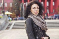 Caucasian kvinna för Beautifil brunett i läderomslag och halsduk w arkivbild