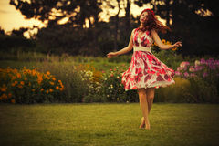caucasian kvinna för brunett i den vita och röda klänningen på parkera i röda och gula blommor på en sommarsolnedgångdans i ängen Royaltyfri Bild