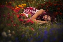 caucasian kvinna för brunett i den vita och röda klänningen på parkera i röda och gula blommor på en sommarsolnedgångdans i ängen royaltyfri fotografi
