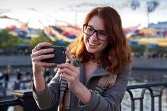 Caucasian kvinna för gullig ung rödhårig man som utomhus tar en selfie på solig dag Härlig ung kvinna som poserar för att le för  royaltyfria bilder