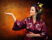 Caucasian kvinna för kimono som fördjupa hennes högra arm Fotografering för Bildbyråer