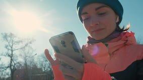 Caucasian kvinna för pannaskott i rosa väljande musik för utomhus- genomkörare i vinter stock video