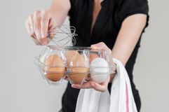 Caucasian kvinna med den svarta skjortan som mycket rymmer en eggbeater och en plast- äggask av fega ägg arkivbild
