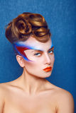 Caucasian kvinna med idérikt smink och frisyr på blått tillbaka Royaltyfria Bilder