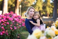 Caucasian kvinna med lilla flickan i händer i rosa trädgård, mamma och mig begrepp, kel som ser till kameran arkivfoto