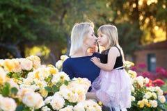Caucasian kvinna med lilla flickan i händer i rosa trädgård, mamma och mig begrepp, kel som till varandra ser royaltyfri fotografi
