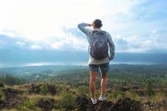 Caucasian kvinna med ryggsäcken som överst står av ett berg och långt borta ser på landskap Royaltyfria Foton