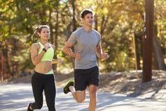 Caucasian kvinna och man som joggar på en landsväg, slut upp fotografering för bildbyråer