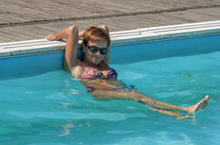 Caucasian kvinna på kanten av att simma den utomhus- pölen Arkivfoto