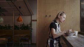 Caucasian kvinna som äter smaskiga nudlar i en lokal kinesisk restaurang med pinnar arkivfilmer