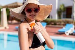 Caucasian kvinna som sätter sol- kräm på hennes skuldra vid pölen under solsken på sommardag Solskyddsfaktor i semester, royaltyfria foton