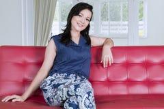 Caucasian kvinna som sitter på soffan fotografering för bildbyråer