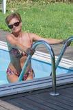 Caucasian kvinnaanseende på trappa av att simma den utomhus- pölen Royaltyfri Foto
