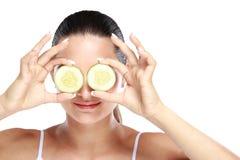 Caucasian kvinnainnehavskivor av gurkan för sminkmaskering royaltyfria foton