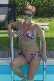 Caucasian kvinnasammanträde på trappa av att simma den utomhus- pölen Royaltyfri Bild