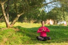 Caucasian kvinnasammanträde under ett träd och meditera Arkivbild