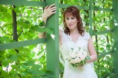 Caucasian kvinnastående med det gröna staketet Royaltyfri Foto