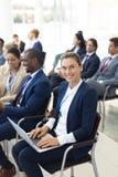 Caucasian kvinnlig ledare som använder bärbara datorn i konferensrum som ler till kameran arkivfoton