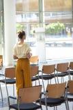 Caucasian kvinnlig ledare som bort ser, medan stå i tomt konferensrum royaltyfri foto