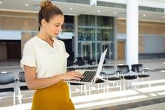 Caucasian kvinnlig ledare som ser datoren, medan stå i tomt konferensrum royaltyfri foto
