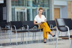 Caucasian kvinnlig ledare som ser den digitala minnestavlan, medan sitta på stol i tomt konferensrum arkivbilder