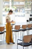Caucasian kvinnlig ledare som ser dokument, medan stå i tomt konferensrum arkivfoto