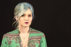 Caucasian kvinnlig modell, ålder 22, blått färgat hår, röd grön och röd skjorta för kanter, Isolerat på svart bakgrund Övretorso  royaltyfri foto