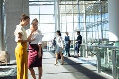 Caucasian kvinnliga ledare som ser dokument, medan stå i modernt kontor arkivbild