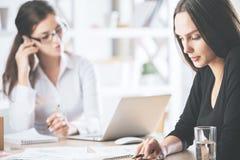 Caucasian kvinnor som gör skrivbordsarbete Arkivfoton