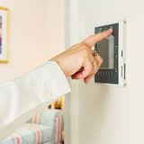 Caucasian lady pressing modern thermostat Stock Images