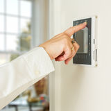 Caucasian lady pressing modern thermostat Royalty Free Stock Image