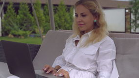 Caucasian lady scrolling on pc outdoors. stock footage