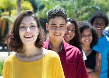 Caucasian and latin and african american and hispanic young adults in a row. Outdoors in summer royalty free stock photography