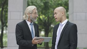 Corporate executives discussing business using digital tablet. Caucasian and latino corporate executives discussing business using digital tablet stock photos
