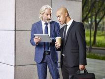 Two corporate executives talking while walking. Caucasian and latino corporate executives discussing business on way to work stock image
