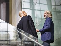 Two corporate executives talking while ascending stairs. Caucasian and latino corporate executives talking chatting while ascending stairs in modern building Royalty Free Stock Image