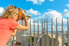Woman looking Eiffel Tower. Caucasian lifestyle traveler looking skyline of Paris with tourist binocular from top of Arc de Triomphe. Blonde tourist woman Royalty Free Stock Photo