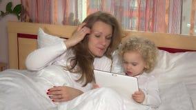 Caucasian liten flicka och moder med minnestavladatoren på säng stock video