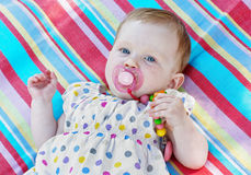 Caucasian little baby girl with multicolored frock Stock Photos