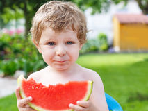 Caucasian little boy with blond hairs eating fresh watermelon in Stock Image