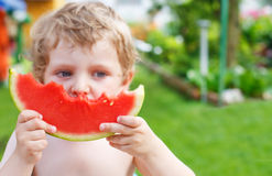 Caucasian little boy with blond hairs eating fresh watermelon in Royalty Free Stock Images