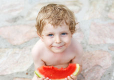 Caucasian little boy with blond hairs eating fresh watermelon in Royalty Free Stock Photography