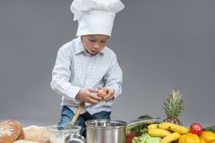 Caucasian Little Boy Crashing Fresh Egg In Cooking Hat. Royalty Free Stock Images