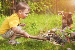 Caucasian Little Boy Dealing With Fire near Firepace Outdoors. Stock Image