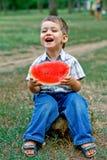Caucasian little boy eats a slice of watermelon Stock Photos