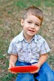 Caucasian little boy eats a slice of watermelon Stock Photo