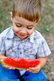 Caucasian little boy eats a slice of watermelon Stock Photos
