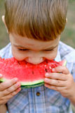 Caucasian little boy eats a slice of watermelon Stock Photo