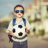 Caucasian little boy standing on the road and holding his soccer Stock Photography